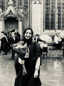 Zehra, outside of The Sheldonian Theatre, in her graduation robes, holding a bouquet of flowers, and smiling